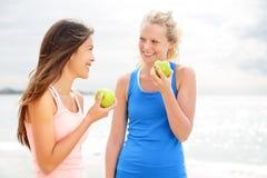 Mujeres sanas de la forma de vida que comen la manzana después de correr Imágenes de archivo libres de regalías