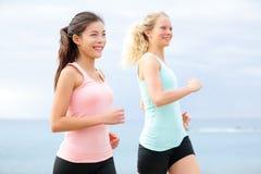 Mujeres sanas de la forma de vida que corren en la playa Imagen de archivo