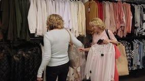 Mujeres shopaholic hermosas que compran ropa en tienda almacen de metraje de vídeo