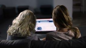 Mujeres shoppping en línea en sitio web usando el ordenador portátil almacen de metraje de vídeo