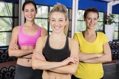 Mujeres sonrientes atléticas que presentan con los brazos cruzados Foto de archivo