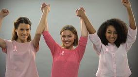Mujeres sonrientes con la cinta rosada que aumenta las manos para arriba, luchando contra cáncer de pecho metrajes