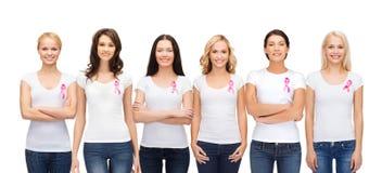 Mujeres sonrientes con las cintas rosadas de la conciencia del cáncer Foto de archivo libre de regalías
