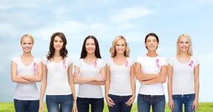Mujeres sonrientes con las cintas rosadas de la conciencia del cáncer Fotografía de archivo
