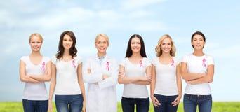 Mujeres sonrientes con las cintas rosadas de la conciencia del cáncer Imagenes de archivo
