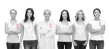 Mujeres sonrientes con las cintas rosadas de la conciencia del cáncer Imagen de archivo libre de regalías
