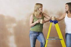 Mujeres sonrientes con las tazas por la escalera de paso fotos de archivo libres de regalías