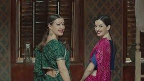 Mujeres sonrientes en la sari que mira detrás sobre hombros metrajes
