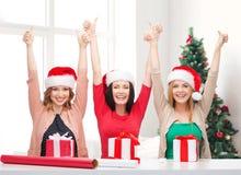 Mujeres sonrientes en los sombreros del ayudante de santa que embalan los regalos Fotos de archivo