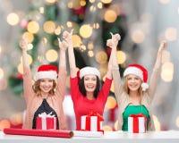 Mujeres sonrientes en los sombreros del ayudante de santa que embalan los regalos Imágenes de archivo libres de regalías