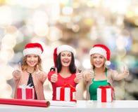 Mujeres sonrientes en los sombreros del ayudante de santa que embalan los regalos Fotografía de archivo