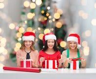 Mujeres sonrientes en los sombreros del ayudante de santa que embalan los regalos Foto de archivo libre de regalías