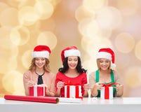 Mujeres sonrientes en los sombreros del ayudante de santa que embalan los regalos Imagen de archivo libre de regalías