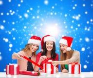 Mujeres sonrientes en los sombreros del ayudante de santa que embalan los regalos Fotos de archivo libres de regalías