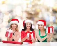 Mujeres sonrientes en los sombreros del ayudante de santa que embalan los regalos Imagen de archivo
