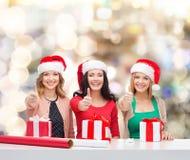 Mujeres sonrientes en los sombreros del ayudante de santa que embalan los regalos Fotografía de archivo libre de regalías