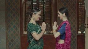 Mujeres sonrientes en sari india que se saludan almacen de video
