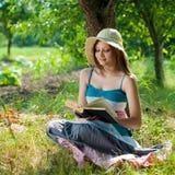 Mujeres sonrientes felices hermosas que leen al aire libre Imagen de archivo