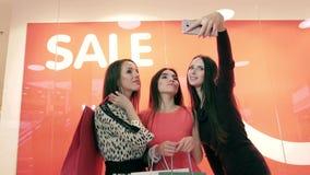 Mujeres sonrientes hermosas que toman imágenes de ellos mismos que se oponen a muestra roja de la venta metrajes