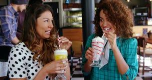 Mujeres sonrientes que comen el smoothie con la paja metrajes