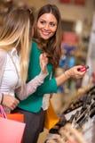 Mujeres sonrientes que compran y que miran cosméticos imágenes de archivo libres de regalías