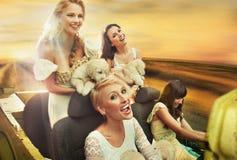 Mujeres sonrientes que conducen un coche Imágenes de archivo libres de regalías