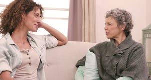 Mujeres sonrientes que hablan sentarse en el sofá metrajes