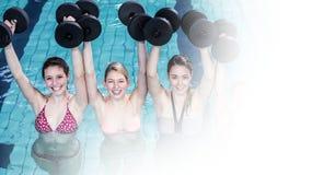 Mujeres sonrientes que levantan pesas de gimnasia en piscina Imagenes de archivo