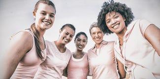 Mujeres sonrientes que llevan el rosa para el cáncer de pecho imagen de archivo libre de regalías