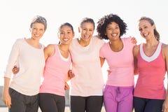 Mujeres sonrientes que llevan el rosa para el cáncer de pecho imagenes de archivo