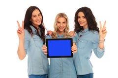 3 mujeres sonrientes que muestran la victoria mientras que presenta el pedregal de la tableta Imagen de archivo libre de regalías
