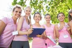 Mujeres sonrientes que organizan el evento para la conciencia del cáncer de pecho Foto de archivo libre de regalías
