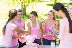 Mujeres sonrientes que organizan el evento para la conciencia del cáncer de pecho Imágenes de archivo libres de regalías