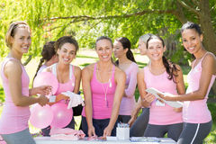 Mujeres sonrientes que organizan el evento para la conciencia del cáncer de pecho imagen de archivo libre de regalías