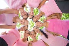 Mujeres sonrientes que organizan el evento para la conciencia del cáncer de pecho imagen de archivo