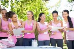 Mujeres sonrientes que organizan el evento para la conciencia del cáncer de pecho Fotos de archivo libres de regalías