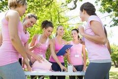 Mujeres sonrientes que organizan el evento para la conciencia del cáncer de pecho Fotografía de archivo libre de regalías