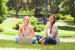 Mujeres sonrientes que se sientan en el parque con un ordenador portátil Imágenes de archivo libres de regalías