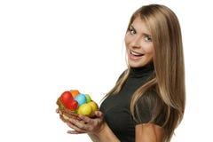 Mujer sonriente que sostiene la cesta con los huevos de Pascua Foto de archivo