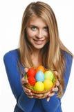 Mujer sonriente que sostiene la cesta con los huevos de Pascua Imagen de archivo libre de regalías