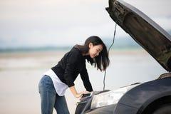 Mujeres subrayadas después de una avería del coche con el triángulo rojo de un coche Fotografía de archivo