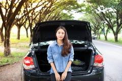Mujeres subrayadas después de una avería del coche con el triángulo rojo de un coche Foto de archivo libre de regalías