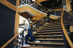 Mujeres tailandesas de los viajeros que caminan para arriba en las escaleras de madera clásicas en restaurante moderno y de lujo fotos de archivo