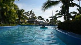 Mujeres tailandesas que nadan y que juegan el agua en piscina en al aire libre del parque del agua metrajes