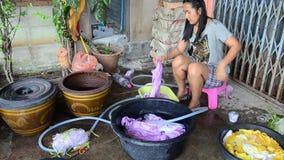 Mujeres tailandesas que se lavan y ropa limpia después de teñir del batik del lazo metrajes