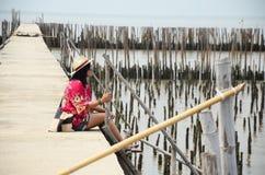Mujeres tailandesas que se sientan solamente en el puente de la calzada en bosque del mangle Foto de archivo libre de regalías