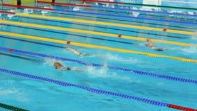 Mujeres tensas de los atletas que nadan la competencia en piscina moderna metrajes