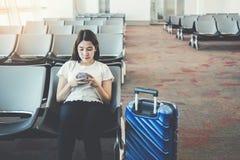 Mujeres turísticas que usan el teléfono en el embarque que espera del aeropuerto internacional para foto de archivo