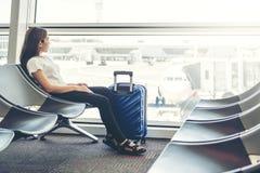 Mujeres tur?sticas que usan el tel?fono en el embarque que espera del aeropuerto internacional para imagenes de archivo