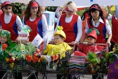 Mujeres y cabritos en carretillas de las compras Foto de archivo